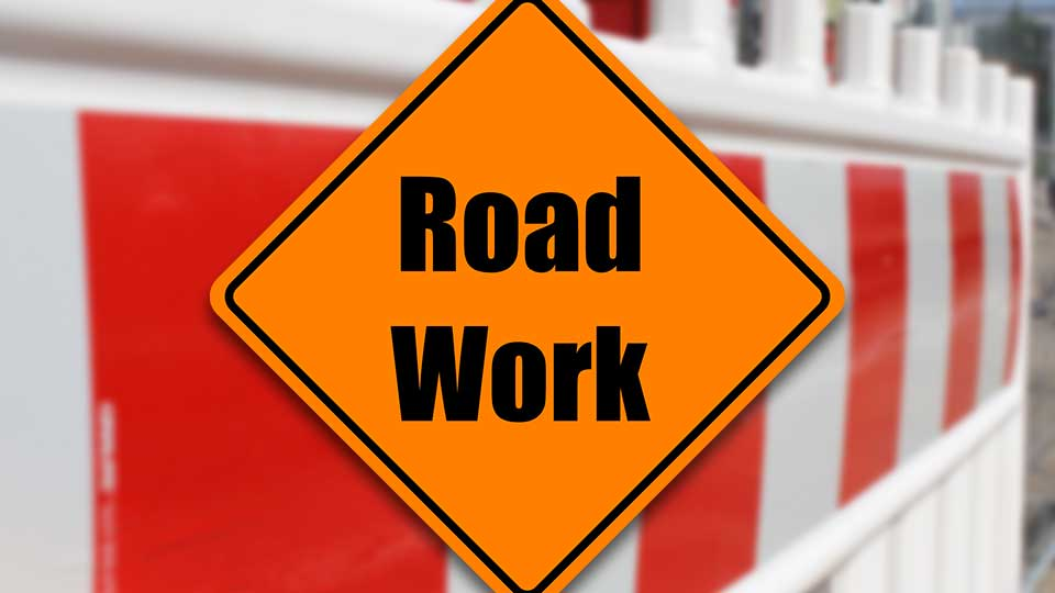 A road work sign in front of an orange road blockade.