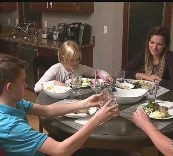 Family sits at dinner table.